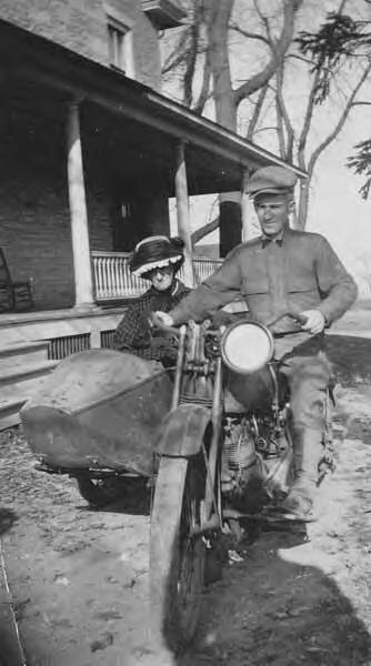 Man_on_motorcycle_with_woman_in_sidecar,_location_unknown,_1921_(INDOCC_793).jpg