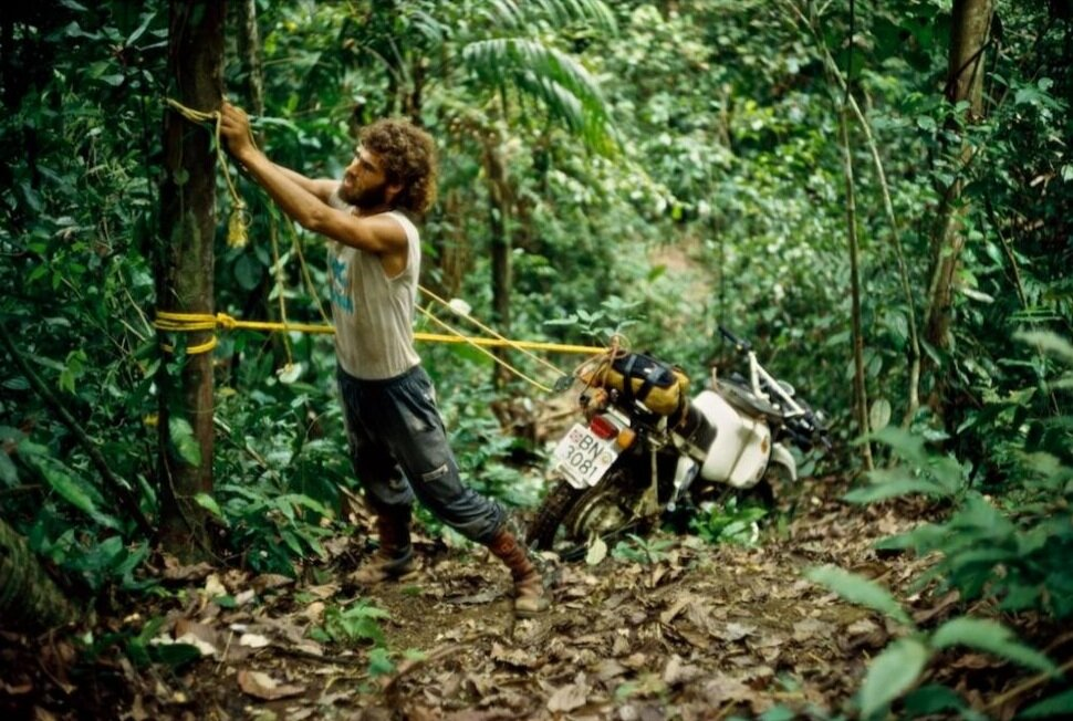 Helge Pederson, one of the most accomplished and inspirational adventure riders, traveled the world for 10 years on his BMW R80 GS named Olga. Here, he hoists Olga through the Darien Gap.  Photo courtesy of Helge Pederson, published with permission.