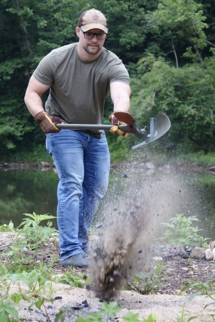 A man shoveling out a fire pit.