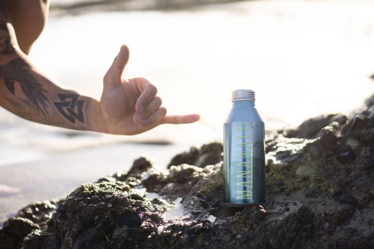 Mananalu Metal Water Bottle on volcanic rocks.