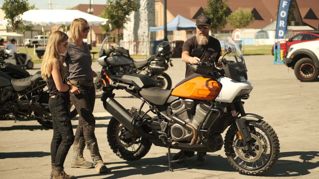 Two women motorcycle riders learn about the Harley Davidson Pan America from a man with a beard.