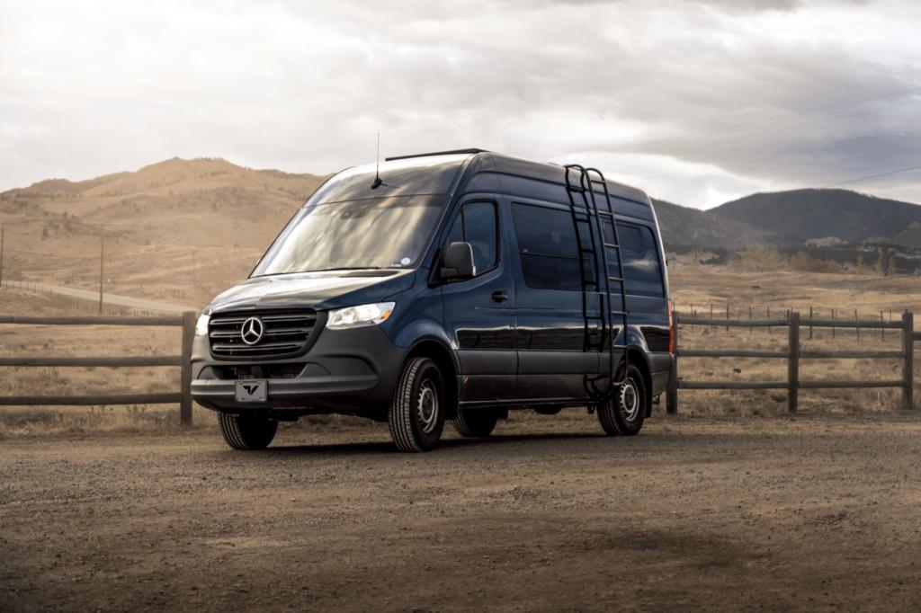 Shows a Mercedes Sprinter van in front of rolling hills.