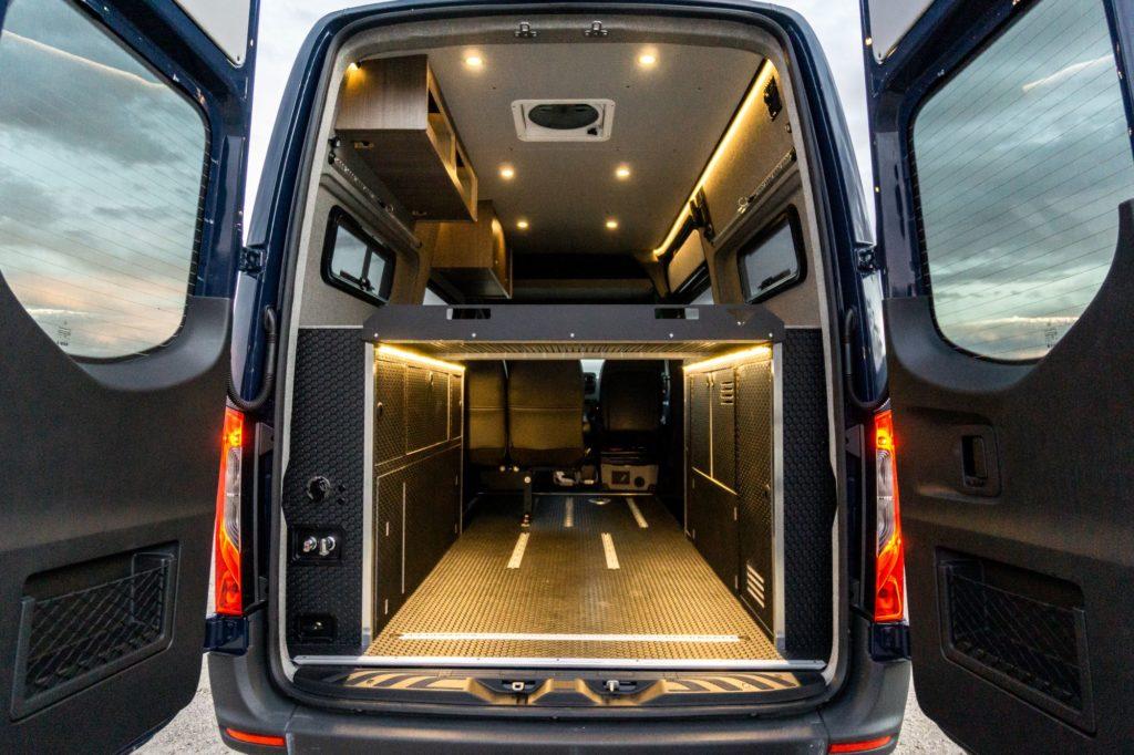 Shows the open rear doors of a customized Sprinter van.