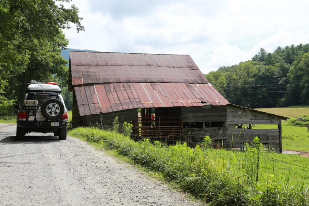A 100 Series Toyota Landcruiser passing an old barn on the Georgia Traverse.