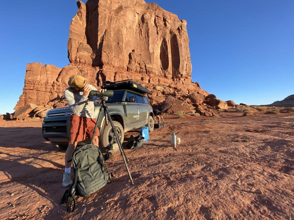 Overlander using a spotting scope in the desert.