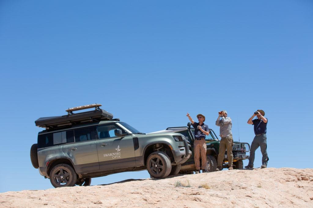 Land Rover Defender and overlanders overlooking the desert.