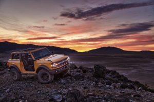 Ford Bronco in desert sunset landscape.