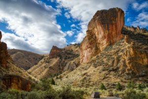 A Subaru next to a large rock formation in Jordan Valley, Oregon